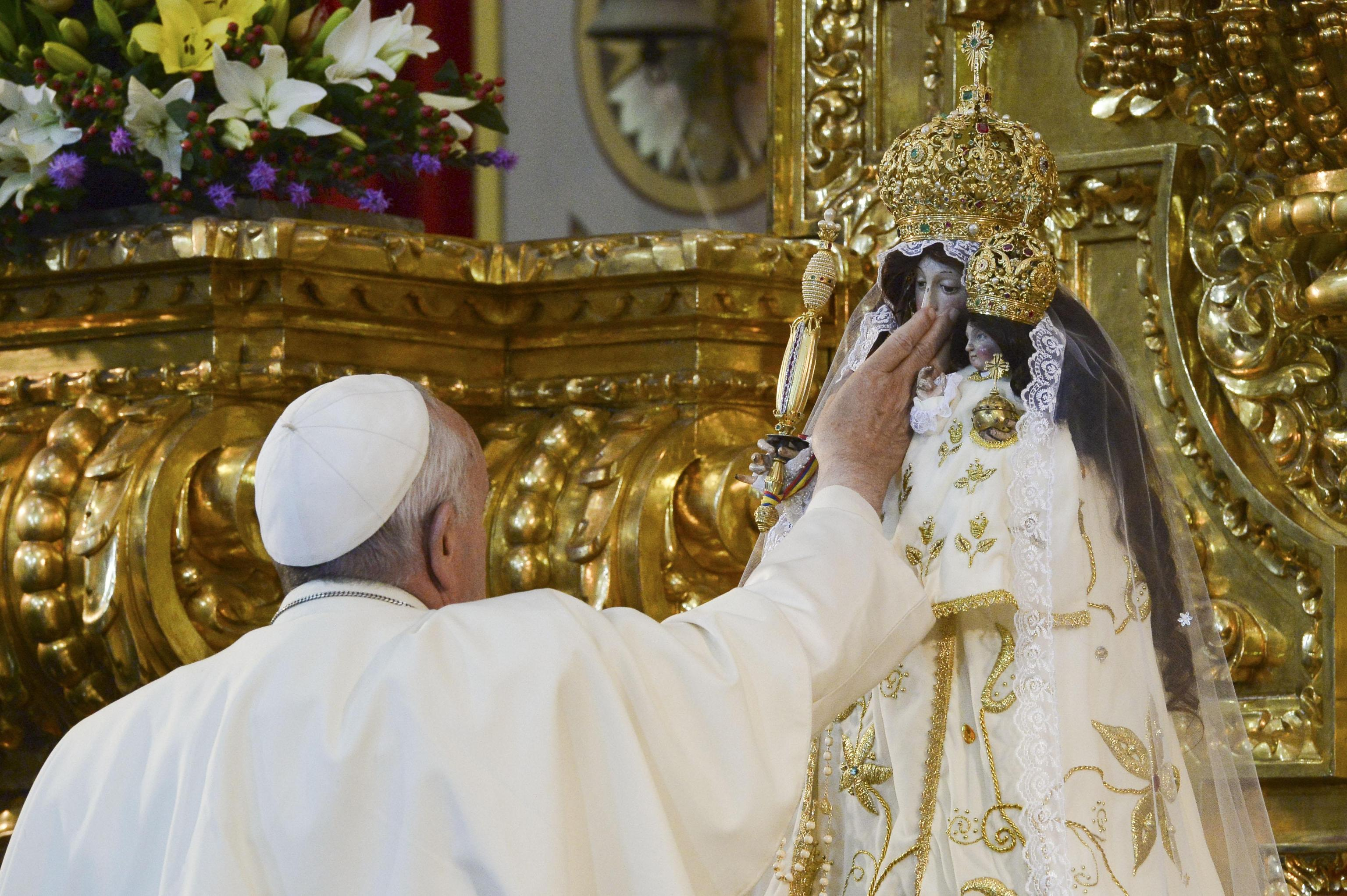 Pope Francis caresses the statue of Our Lady of Quinche