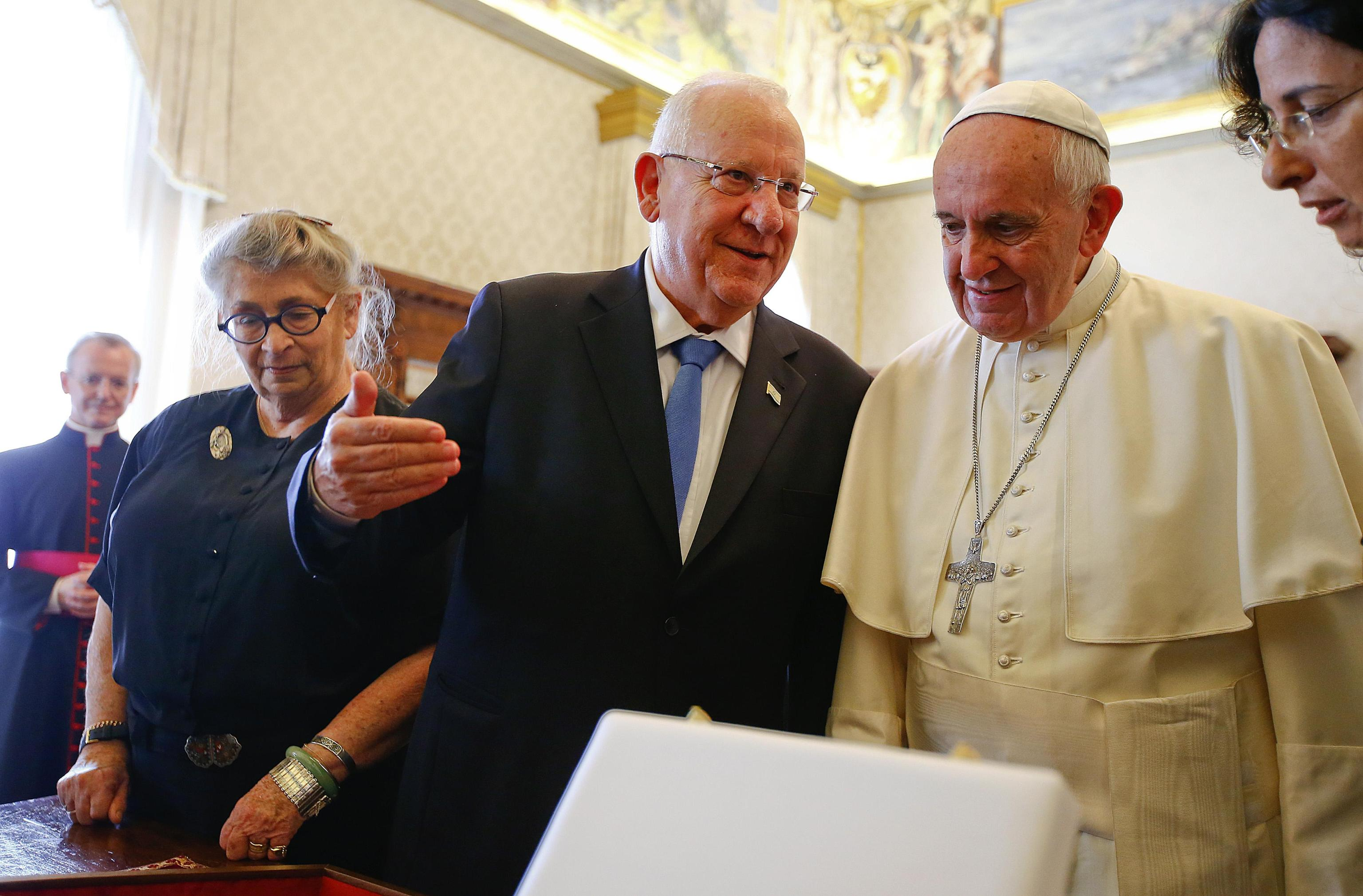 Pope Francis listens to Israel's President Reuven Rivlin as they exchange gifts during a private audience in the Pontiff's private library at the Vatican